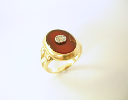 Shows a ring with dark red Carnelian cabochon which has a chip in it.