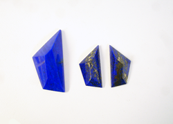 A freeform shaped Lapis faceted cabochon.