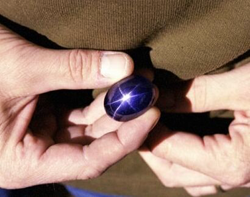 Photo of the gem dealer holding the large star sapphire.