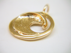 A gold pendant in the round shape of a wave.