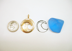 The round gold pendant next to a piece of rough blue topaz which we will use for carving.