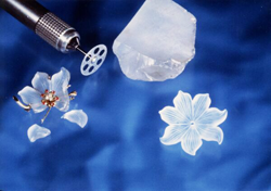 Picture showing a broken Quartz flower carving and a new one just like the broken one and also the carving tool that was used to make it.