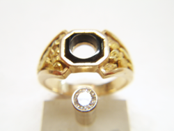 Photo of a nugget style ring with a black Onyx in the middle and a Diamond in a gold tube next to the ring.