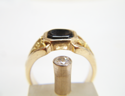 Side view of a nugget style ring with a black Onyx in the middle and a Diamond in a gold tube next to the ring.