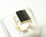 Photo of a ring with a rectangle black Onyx with 2 small holes drilled in it.