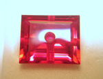 Photo of a red synthetic Ruby with a hole drilled in the center.