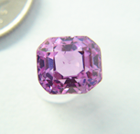 Photo of a poorly cut emerald cut pink Sapphire which is windowed.