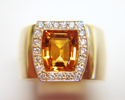 A bright orangy Yellow citrine in a ring surrounded by diamonds.