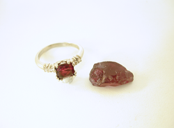 A piece of rough uncut Rhodolite Garnet next to the ring with the broken one.
