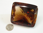 A large cushion shaped brownish colored faceted Topaz.