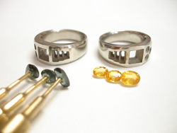2 white gold rings and 3 blue sapphires glued to dop sticks and 3 yellow sapphires.