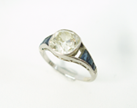 A white gold antique Diamond ring with blue Sapphires, and one is missing.