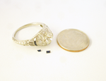 An antique diamond ring and 2 very tiny blue Sapphires sitting next to the ring.