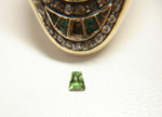 An oval antique ring with green stones. One of the green stones is missing.