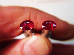 Shows me holding 2 oval Rubies which are on dop sticks.