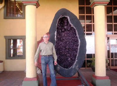 Photo of Denton next to a large Amethyst geode at the Tucson gem show.