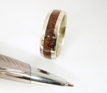 A 14 karat white gold wedding band inlaid 360 degrees around with petrified dinosaur bone.