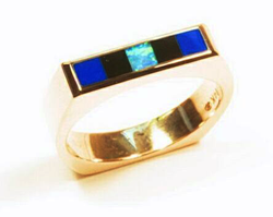 Ring inlaid with 5 inlays. 2 squares are Lapis. 2 are black Onyx. And the center square is Opal.