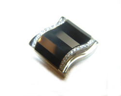 It is now finished and set into the cufflink mounting which is white gold and has diamonds on each side of the Onyx.