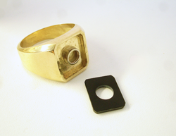 Photo of a gold men's ring with a round tube set in the middle and also an emerald cut Black Jade.