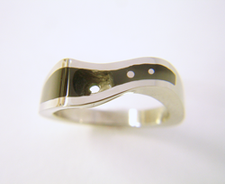 Photo of the ring which has had holes drilled to put the Diamond and also 2 small white gold dots.