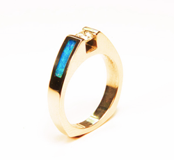 A round diamond in the center of a simple white gold ring and a narrow rectangular Opal inlaid on each side.