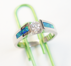 A round diamond in the center of a simple yellow gold ring and a narrow rectangular Opal inlaid on each side.