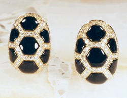 A pair of gold earrings which are inlaid with several hexagonal black Onyx inlays which have slight domes on the top.