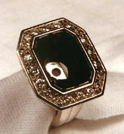 The carved black jade is set into the ring but the diamond is not yet in the center.