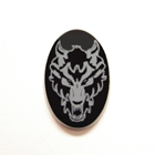 Photo of an oval black Onyx with the white image of a wolf on it which was made with a laser.