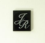 Photo of a rectangular black Onyx stone with the initials J R in white which were made with a laser.