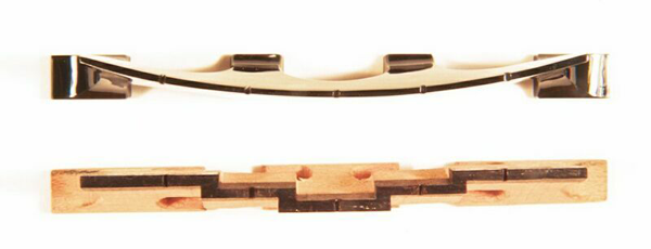 A wooden banjo bridge and one made from black jade from different angle.