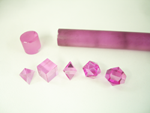 Small photo of 5 pink synthetic sapphires which we faceted into geometric shapes.