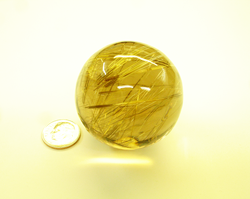 Shows the Rutillated Quartz sphere sitting next to a dime for size comparison.