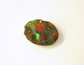 A black opal which is chipped and needs to be repaired.