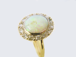Photo of an Opal ring surrounded by Diamonds with a piece of the Opal missing.