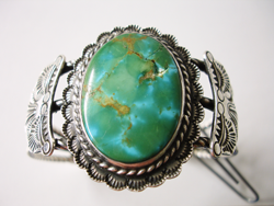 Photo of a large broken Turquoise cabochon in a silver bracelet.