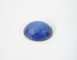 Photo of a blue Linde Star Sapphire cabochon which needs to be re-polished and is very dull looking.