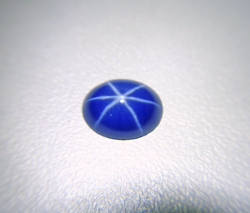 Photo of a blue Linde Star Sapphire cabochon which has been re-polished and now shows a nice sharp star.