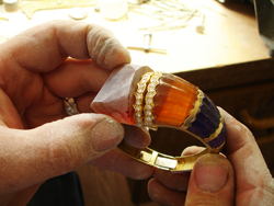 Photo of our carver carving the synthetic Citrine to fit the bracelet.