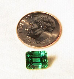 Picture of an Emerald next to a dime.