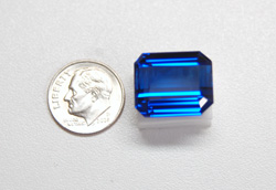 The finished Tanzanite sitting next to a dime.