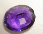 Photo of a purple oval Amethyst with a large chip in the pavilion.