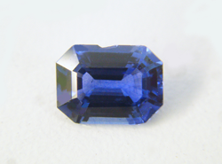 An emerald cut blue Sapphire with a chip along the side.