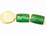 Photo of a pair of cushion green Tourmaline. One of them has a chip.