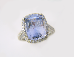Shows the same light blue Sapphire which has now been repaired and is sitting in the diamond ring mounting.