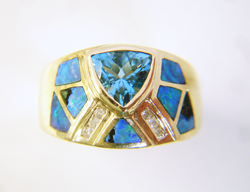 Photo of a ring with a blue Topaz center stone and many triangular Opal inlays, some of which are broken.