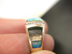Photo of a ring with one Opal inlay and a blank area where 2 Opal inlays have fallen out.