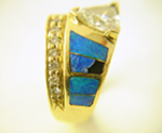 Photo of an Opal ring with a trillion diamond a brokenopal inlay.