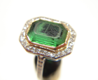 Picture of a green stone with a scratched table which is set in a ring.